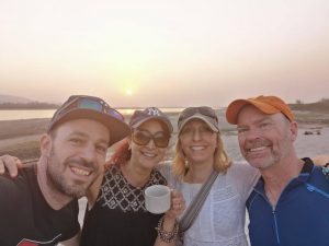 Four friends on a beach, smiling. Two women and two men. All of them in baseball caps.