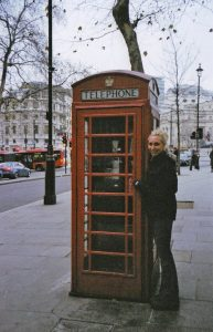 Melissa is to the right of a traditional London telephone phone booth. She is dressed in jeans and a black jacket.