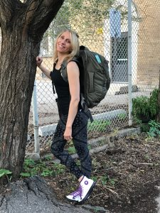 Melissa Rodway standing against a tree, wearing a brown backpack.