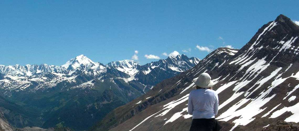 A woman stands off to the right hand side of the picture. Her back is to the camera. She is wearing a long white sleeved shirt and a white bucket hat. She is looking out toward numerous snow capped mountain peaks. This is the Alps.