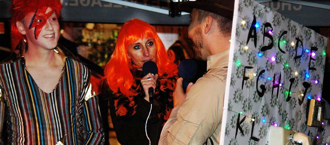 Melissa in an orange wig holding a microphone. She is standing outside, interviewing on Church Street in Toronto for Hallowe'en. She has Ziggy Stardust behind her and someone dressed as a rotary telephone in front of her.
