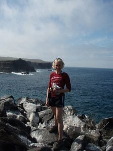Melissa is standing on some rocks with the ocean out behind her, and an escarpment in the distance. She is in shorts and a long sleeved top. The sky is blue with wispy clouds behind her.