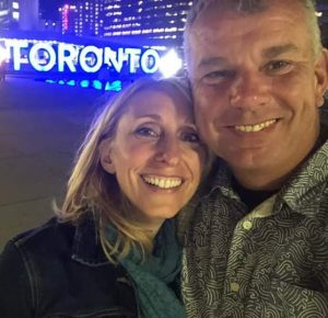 A man and a woman (Melissa) meet up in front of Toronto sign. They are smiling for the camera. They are friends.