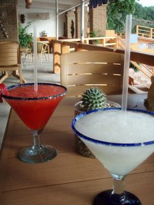 A red and a white margarita sit on a table on an outdoor patio. There is no one in the picture, just empty tables. It gives the essence of a warm climate.