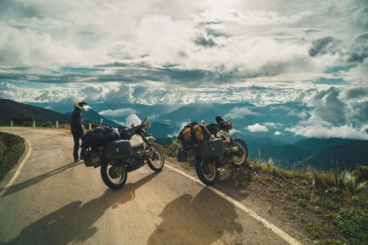 Two motorbikes on the side of a road, looking over a vista of mountains and clouds.