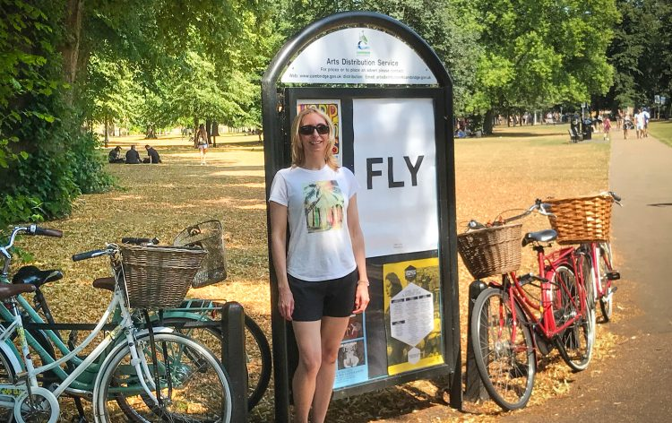 Melissa Rodway - standing in front of a sign that says FLY. It is a summer day, and there are bikes on either side of Melissa and the sign.