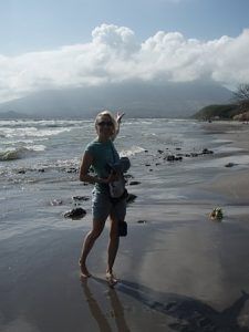 Melissa is on a beach in Nicaragura, pointing to the volcano behind her. It is a sunny day, but there are beautiful white fluffy clouds in the sky.