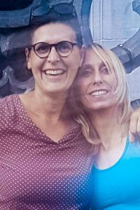 Two women standing together and smiling. One is brunette with glasses, the other (Melissa) is blonde. They are beside each other, smiling for the camera.