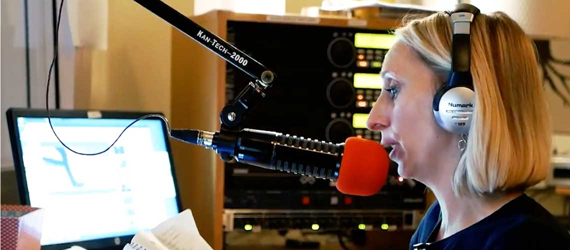 Melissa is speaking into a red microphone in a sound booth, she has headphones on and is reading from a paper. There is a computer screen in the background as well as a soundboard.
