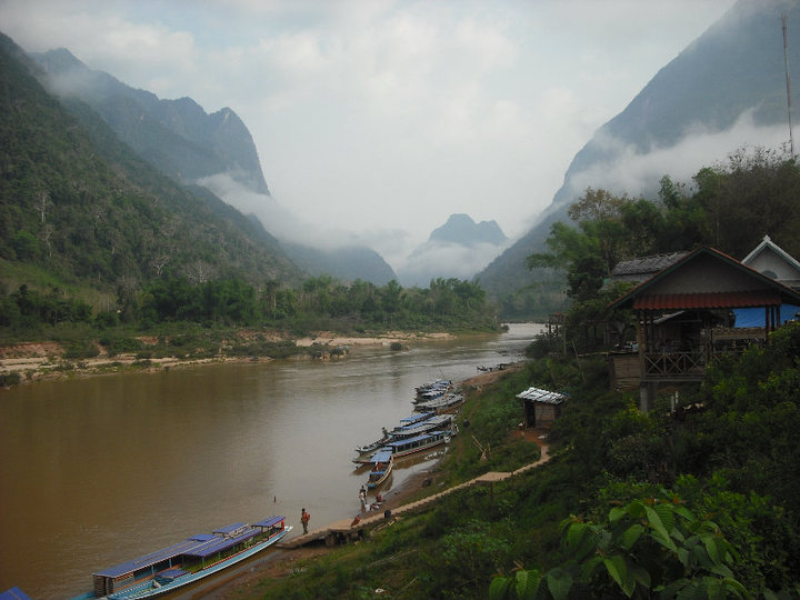 Picture of river, mountains, clouds, and longtail boats in Laos, Southeast Asia.